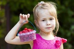 Πορτρέτο ενός μικρού μικρού καλαθιού παιδιών κοριτσιών holdind των ώριμων ras Στοκ Εικόνα