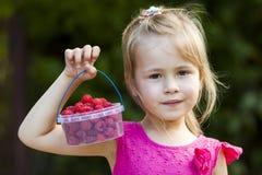 Πορτρέτο ενός μικρού μικρού καλαθιού παιδιών κοριτσιών holdind των ώριμων ras Στοκ φωτογραφία με δικαίωμα ελεύθερης χρήσης