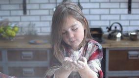 Πορτρέτο ενός μικρού κοριτσιού που λερώνεται βαριά στο φυσώντας αλεύρι αλευριού από το φοίνικά της Χαριτωμένο κορίτσι που έχει τη φιλμ μικρού μήκους