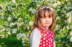 Πορτρέτο ενός μικρού κοριτσιού σε έναν οπωρώνα άνθησης Apple Στοκ φωτογραφία με δικαίωμα ελεύθερης χρήσης