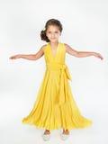 πορτρέτο ενός μικρού κοριτσιού σε ένα κίτρινο φόρεμα Στοκ Εικόνες