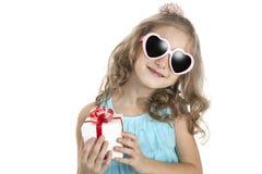 Πορτρέτο ενός μικρού κοριτσιού στα ρόδινα γυαλιά ηλίου με το κιβώτιο δώρων Στοκ Φωτογραφία