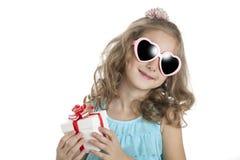 Πορτρέτο ενός μικρού κοριτσιού στα ρόδινα γυαλιά ηλίου με το κιβώτιο δώρων Στοκ φωτογραφίες με δικαίωμα ελεύθερης χρήσης