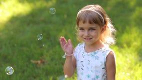 Πορτρέτο ενός μικρού κοριτσιού στο διαφορετικό χρώμα ματιών στο πάρκο στο ηλιοβασίλεμα απόθεμα βίντεο