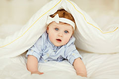 Πορτρέτο ενός μικρού μωρού κοριτσιών με τα μπλε μάτια σε ένα ριγωτό μπλε Στοκ εικόνα με δικαίωμα ελεύθερης χρήσης