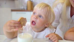 Πορτρέτο ενός μικρού παιδιού κοριτσιών με την ξανθή τρίχα και τη χαριτωμένη κουζίνα συνεδρίασης προσώπου χαμόγελου στο σπίτι, που φιλμ μικρού μήκους