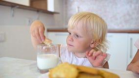 Πορτρέτο ενός μικρού παιδιού κοριτσιών με την ξανθή τρίχα και το χαριτωμένο εσωτερικό κουζινών συνεδρίασης προσώπου χαμόγελου στο φιλμ μικρού μήκους