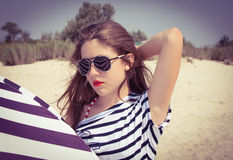 Πορτρέτο ενός μοντέρνου κοριτσιού σε μια ριγωτή μπλούζα και τα γυαλιά ηλίου β στοκ φωτογραφία με δικαίωμα ελεύθερης χρήσης