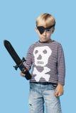 Πορτρέτο ενός νέου αγοριού στο ξίφος εκμετάλλευσης κοστουμιών πειρατών πέρα από το μπλε υπόβαθρο Στοκ εικόνες με δικαίωμα ελεύθερης χρήσης