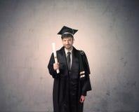 Πορτρέτο ενός νέου απόφοιτου φοιτητή στο βρώμικο υπόβαθρο Στοκ φωτογραφίες με δικαίωμα ελεύθερης χρήσης