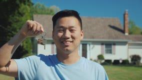 Πορτρέτο ενός νέου ασιατικού ατόμου με ένα κλειδί σπιτιών στο χέρι του Εξέταση τη κάμερα στα πλαίσια του νέου σπιτιού του στοκ φωτογραφία με δικαίωμα ελεύθερης χρήσης