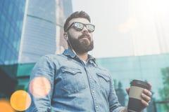 Πορτρέτο ενός νέου γενειοφόρου επιχειρηματία hipster στα γυαλιά ηλίου και τη στάση πουκάμισων τζιν υπαίθρια, που κρατά το φλιτζάν Στοκ Εικόνα