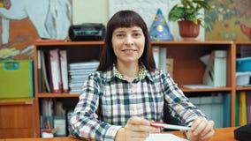 Πορτρέτο ενός νέου δασκάλου στο υπόβαθρο των ραφιών με τα έγγραφα φιλμ μικρού μήκους