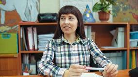 Πορτρέτο ενός νέου δασκάλου στο υπόβαθρο των ραφιών με τα έγγραφα απόθεμα βίντεο