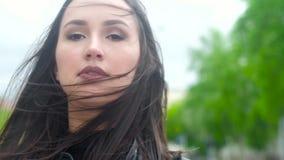 Πορτρέτο ενός νέου ελκυστικού κοριτσιού με τη μακριά σκοτεινή τρίχα, κόκκινο κραγιόν στα χείλια της στο υπόβαθρο μιας οδού πόλεων φιλμ μικρού μήκους