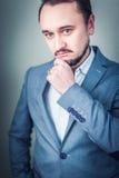 Πορτρέτο ενός νέου επιχειρηματία στο γκρίζο υπόβαθρο Στοκ Εικόνες