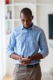 Πορτρέτο ενός νέου επιχειρησιακού ατόμου αφροαμερικάνων που χρησιμοποιεί έναν κινητό Στοκ Εικόνες