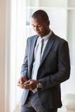 Πορτρέτο ενός νέου επιχειρησιακού ατόμου αφροαμερικάνων που χρησιμοποιεί έναν κινητό Στοκ Φωτογραφία