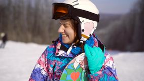 Πορτρέτο ενός νέου, ευτυχούς κοριτσιού με ένα σνόουμπορντ στα χέρια της Χειμερινή ηλιόλουστη ημέρα, γύρω από το βουνό, χιονοδρομι απόθεμα βίντεο