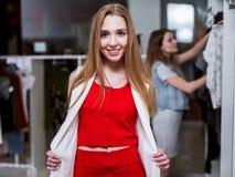 Πορτρέτο ενός νέου θηλυκού προτύπου που κοιτάζει στον καθρέφτη που φορούν το σύνολο συντονισμού κόκκινων κορυφών και φουστών και  Στοκ φωτογραφία με δικαίωμα ελεύθερης χρήσης