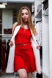 Πορτρέτο ενός νέου θηλυκού προτύπου που κοιτάζει στον καθρέφτη που φορούν το σύνολο συντονισμού κόκκινων κορυφών και φουστών και  Στοκ Εικόνες