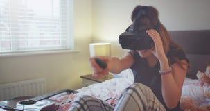 Πορτρέτο ενός νέου κοριτσιού εφήβων στις πυτζάμες που παίζει με ένα VR είναι πολύ εντυπωσιασμένη για το παιχνίδι και την εξερεύνη απόθεμα βίντεο