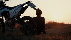 Πορτρέτο ενός νέου κοριτσιού που κάθεται την κλίση σε ένα αθλητικό ποδήλατο και θαυμάζει το ηλιοβασίλεμα απόθεμα βίντεο