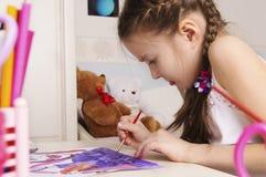 Πορτρέτο ενός νέου κοριτσιού που σύρει μια εικόνα στο χώρο για παιχνίδη της Στοκ Φωτογραφία