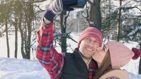 Πορτρέτο ενός νέου μοντέρνου ζεύγους που κάνει selfie σε ένα κόκκινα πουκάμισο και ένα καπέλο, σε έναν ήλιο χειμερινών πάρκων φιλμ μικρού μήκους
