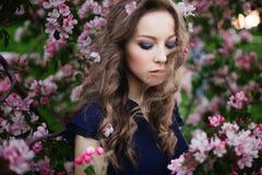 Πορτρέτο ενός νέου σγουρός-μαλλιαρού κοριτσιού με τις ιδιαίτερες προσοχές σε ένα μπλε φόρεμα που στέκεται μεταξύ ενός ανθίζοντας  Στοκ Φωτογραφίες