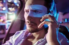 Πορτρέτο ενός νέου τύπου που οδηγά μέσω της πόλης στη νύχτα Στοκ Φωτογραφία