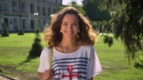 Πορτρέτο ενός νέου χαμόγελου, καυκάσιο brunette γέλιου στο πάρκο, πανεπιστήμιο στο υπόβαθρο φιλμ μικρού μήκους