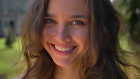 Πορτρέτο ενός νέου χαμόγελου, καυκάσιο brunette γέλιου στο πάρκο, πανεπιστήμιο στο υπόβαθρο απόθεμα βίντεο