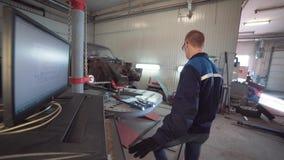 Πορτρέτο ενός νέου όμορφου μηχανικού αυτοκινήτων στο εργαστήριο αυτοκινήτων, στο υπόβαθρο ενός σπασμένου αυτοκινήτου Έννοια: μηχα απόθεμα βίντεο