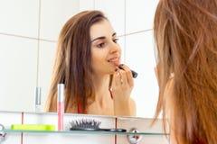Πορτρέτο ενός νέου brunette χαμόγελου που καθρέφτης χειλικού κραγιόν χρωστικών ουσιών Στοκ εικόνες με δικαίωμα ελεύθερης χρήσης