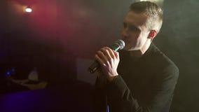 Πορτρέτο ενός νεαρού άνδρα με ένα μικρόφωνο σε ένα υπόβαθρο του καπνού σε ένα σκοτεινό δωμάτιο απόθεμα βίντεο