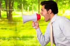 Πορτρέτο ενός νεαρού άνδρα που κραυγάζει με megaphone, σε ένα θολωμένο πράσινο υπόβαθρο Στοκ Εικόνες