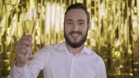 Πορτρέτο ενός νεαρού άνδρα σε ένα χρυσό υπόβαθρο το άτομο χαμογελά και άντεξε μια δεξαμενή της σαμπάνιας 4K απόθεμα βίντεο