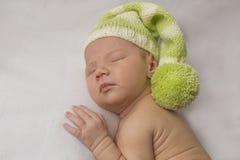Πορτρέτο ενός νεογέννητου αγοριού ύπνου σε ένα πράσινο καπέλο Στοκ Εικόνες
