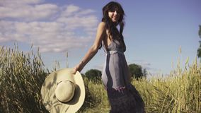 Πορτρέτο ενός ξένοιαστου νέου όμορφου κοριτσιού σε έναν τομέα με ένα καπέλο αχύρου Νέα γυναίκα που χαμογελά παιχνιδιάρικα στη κάμ απόθεμα βίντεο