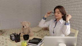 Πορτρέτο ενός οικογενειακού γιατρού στο γραφείο στον εργασιακό χώρο με ένα στηθοσκόπιο απόθεμα βίντεο