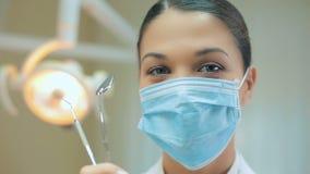 Πορτρέτο ενός οδοντιάτρου στη μάσκα με τα εργαλεία απόθεμα βίντεο