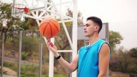 Πορτρέτο ενός παίχτης μπάσκετ που περιστρέφει μια καλαθοσφαίριση στην παιδική χαρά οδών Σε αργή κίνηση πυροβολισμός φιλμ μικρού μήκους