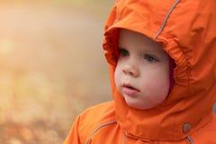 Πορτρέτο ενός παιδιού σε μια κουκούλα και θερμά ενδύματα στοκ εικόνες