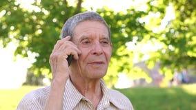Πορτρέτο ενός παππού με το τηλέφωνο στο πάρκο απόθεμα βίντεο