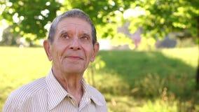 Πορτρέτο ενός παλαιού παππού σε ένα ηλιόλουστο πάρκο φιλμ μικρού μήκους