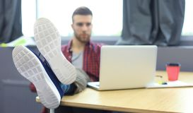 Πορτρέτο ενός πολύ χαλαρωμένου νέου σχεδιαστή που κλίνει πίσω στο γραφείο του και που βάζει τα πόδια του επάνω το γραφείο του στο Στοκ Φωτογραφία