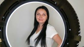 Πορτρέτο ενός πολύ όμορφου μπλε-eyed προτύπου γυναικών με τη μακροχρόνια μαύρη τοποθέτηση τρίχας μπροστά από τη κάμερα φιλμ μικρού μήκους