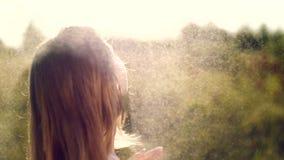 Πορτρέτο ενός προκλητικού, όμορφου νέου ξανθού κοριτσιού, κάτω από μια ψιλή θερινή βροχή, στον ήλιο ακτίνες, σε ένα πράσινο λιβάδ φιλμ μικρού μήκους