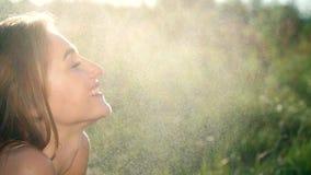 Πορτρέτο ενός προκλητικού, όμορφου νέου ξανθού κοριτσιού, κάτω από μια ψιλή θερινή βροχή, στον ήλιο ακτίνες, σε ένα πράσινο λιβάδ απόθεμα βίντεο